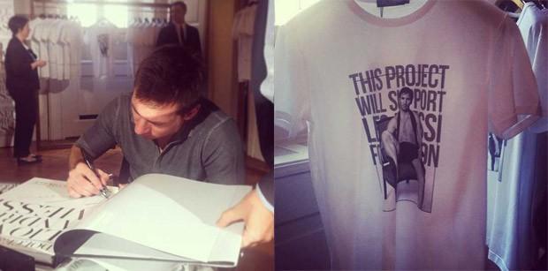 Messi autografando o livro e uma das camisetas